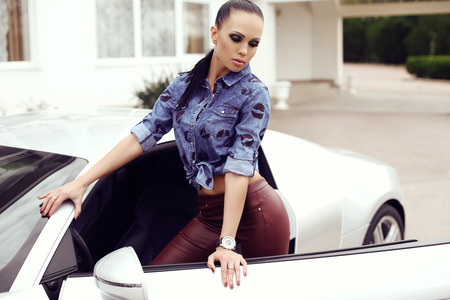 long pants: fashion outdoor photo of sexy beautiful woman with dark hair in  leather pants and jeans shirt posing beside luxurious auto Stock Photo