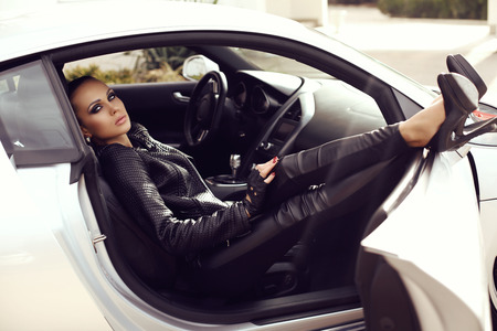 fashion outdoor photo of sexy beautiful woman with dark hair in black leather clothes posing in luxurious auto