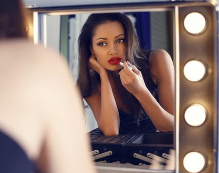 red lips: moda foto interior de la mujer sensual hermosa con el pelo oscuro que hace maquillaje en la sala de maquillaje, mirando el espejo