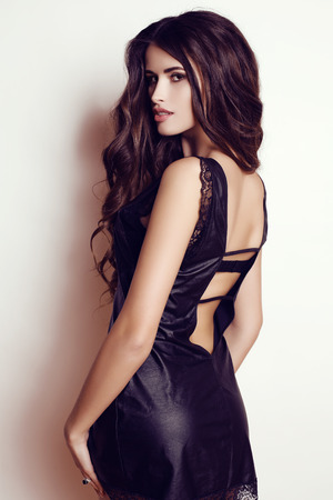 fashion photo of beautiful woman wtih luxurious dark hair in elegant black dress posing in studio
