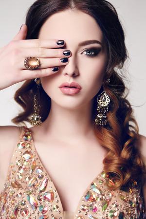 mujeres fashion: estudio de moda foto de la hermosa mujer sensual con el pelo oscuro con un vestido de lentejuelas de lujo y bijou