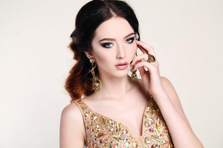 sequin: fashion studio photo of beautiful sensual woman with dark hair wearing luxurious sequin dress and bijou