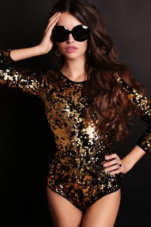 schöne frauen: Mode-Foto der schönen sexy Mädchen mit luxuriösen langen dunklen Haaren trägt Pailletten-Korsett und Sonnenbrille, posiert im Studio