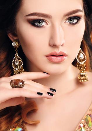 bijou: fashion studio photo of beautiful sensual woman with dark hair and  bright makeup with bijou Stock Photo