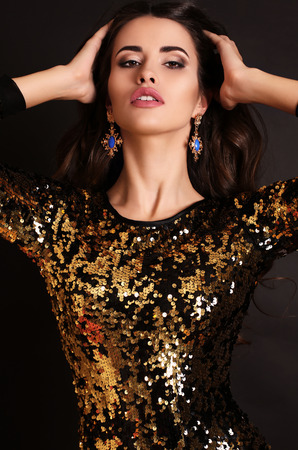 slim girl: fashion photo of beautiful sexy girl with luxurious long dark hair wearing sequin corset,posing in studio