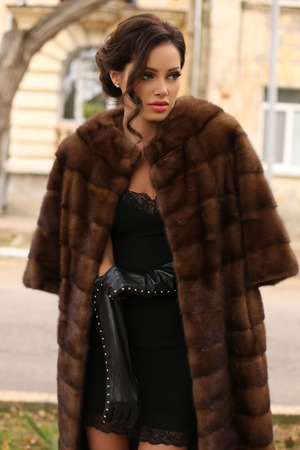 sexy fur: fashion outdoor photo of sexy glamour woman with dark hair wearing luxurious fur coat and leather gloves,posing  in autumn park
