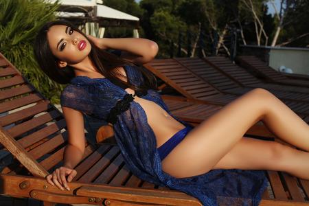 pose sensual: fashion outdoor photo of beautiful sensual woman with dark hair wearing elegant bikini and lace robe posing beside swimming pool Stock Photo