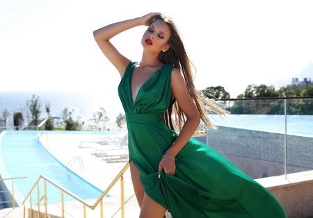 fashion outdoor photo of beautiful young woman with long blond hair in luxurious green silk dress posing beside swimming pool Stock Photo