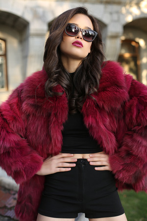 outdoor glamour: fashion outdoor photo of sexy glamour woman with dark hair wearing luxurious red fur coat,posing  in autumn park Stock Photo