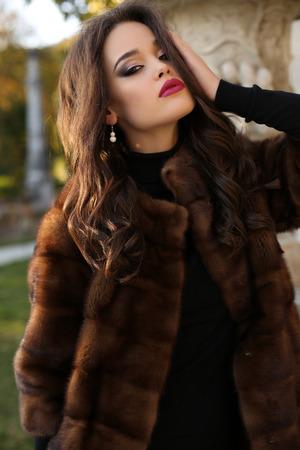 femme brune sexy: mode photo en plein air de glamour sexy avec des cheveux noirs portant un manteau de fourrure de luxe, posant dans le parc de l'automne