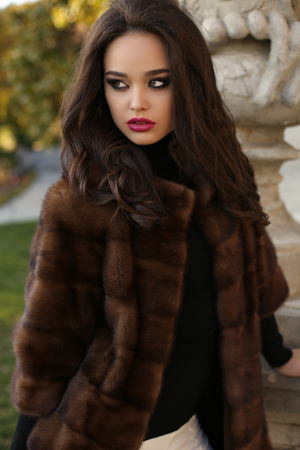 sexy glamour: fashion outdoor photo of sexy glamour woman with dark hair wearing luxurious red fur coat,posing  in autumn park Stock Photo