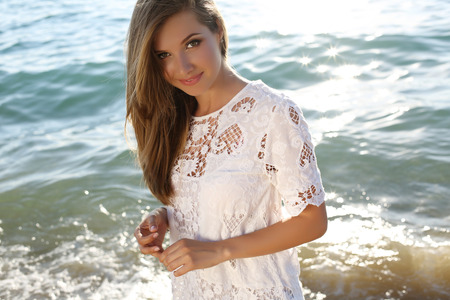 fashion outdoor photo of beautiful sexy girl with blond hair wears elegant dress posing on summer beach Stock Photo