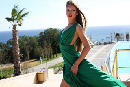 beautiful dress: fashion outdoor photo of beautiful young woman with long blond hair in luxurious green silk dress posing beside swimming pool Stock Photo