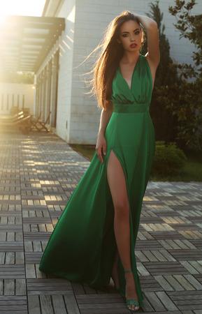 Mode im Freien Foto von schöne sinnliche Frau mit dunklen Haaren tragen elegante Seidenkleid zu Fuß durch die Straße