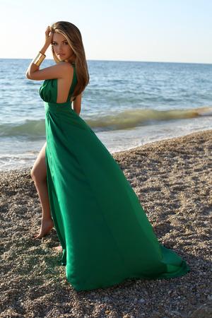 niñas bonitas: moda foto al aire libre de la hermosa chica sexy con el pelo rubio lleva verde lujoso vestido de seda posando en la playa de verano