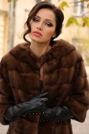 leather coat: fashion outdoor photo of sexy glamour woman with dark hair wearing luxurious fur coat and leather gloves,posing  in autumn park