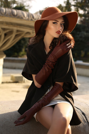 falda: moda foto al aire libre de la señora hermosa con el pelo oscuro que desgasta la capa elegante, guantes de cuero y sombrero de fieltro, que presenta en parque del otoño