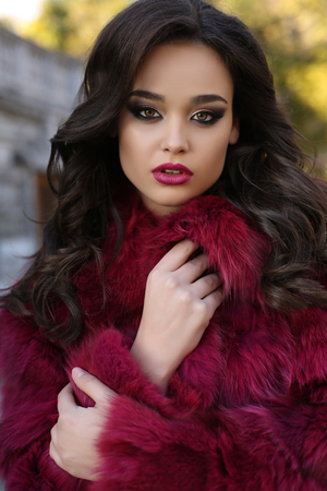 fashion outdoor photo of sexy glamour woman with dark hair wearing luxurious red fur coat,posing  in autumn park 스톡 콘텐츠