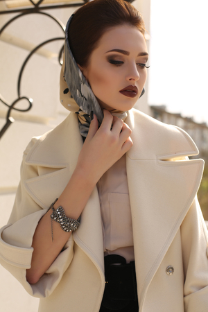 head scarf: fashion outdoor photo of beautiful lady with dark hair wearing elegant coat and silk scarf on head,posing in autumn park