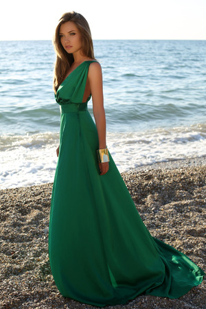 woman beach dress: fashion outdoor photo of beautiful sexy girl with blond hair wears luxurious green silk dress posing on summer beach