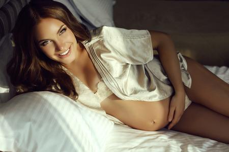 mujer en la cama: Foto interior de la mujer embarazada hermosa con el pelo oscuro que llevaba ropa interior elegante que presenta en el dormitorio Foto de archivo