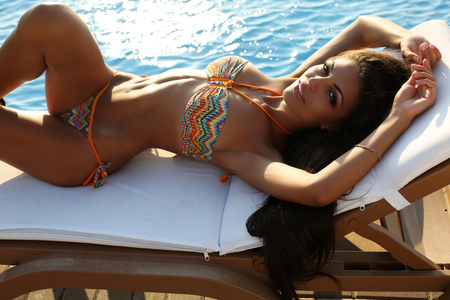 fashion outdoor photo of beautiful sensual woman with dark hair wearing elegant bikini, posing beside swimming pool