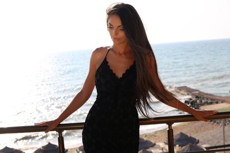 all'aperto foto di moda di bella donna sensuale con i capelli scuri che indossa elegante abito nero, in posa accanto a mare