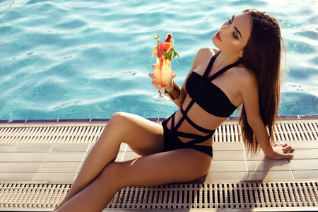 sensual: fashion outdoor photo of beautiful sensual woman with dark hair wearing elegant bikini, posing beside swimming pool with cocktail