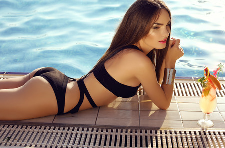 tanned: fashion outdoor photo of beautiful sensual woman with dark hair wearing elegant bikini, posing beside swimming pool with cocktail
