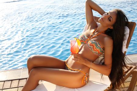 swimsuit model: fashion outdoor photo of beautiful sensual woman with dark hair wearing elegant bikini, posing beside swimming pool with cocktail