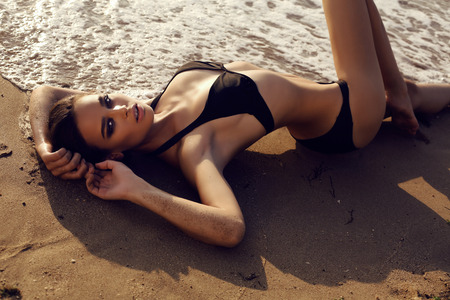 sexy girl posing: fashion outdoor photo of beautiful sexy girl with dark hair and tanned skin wears black bikini relaxing on summer beach Stock Photo