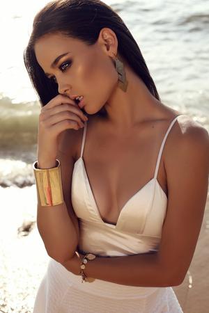 黒い髪、日焼けした肌を持つ美しいセクシーな女の子のファッション屋外写真は夏のビーチでリラックスしたエレガントなドレスを着ています。