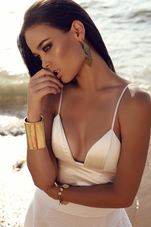 fashion outdoor photo of beautiful sexy girl with dark hair and tanned skin wears elegant dress relaxing on summer beach Archivio Fotografico