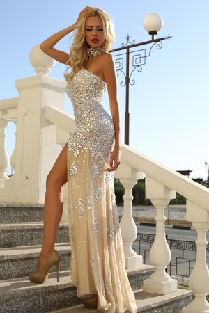 fashion outdoor photo of elegant beautiful woman with blond hair in luxurious sequins dress and silver accessories,posing in summer park
