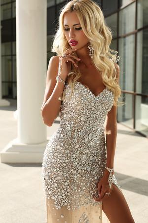 cabello rubio: moda foto al aire libre de la mujer hermosa elegante con el pelo rubio en vestido de lentejuelas de plata y accesorios de lujo, posando en el parque de verano
