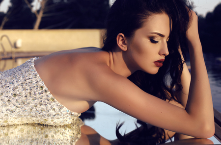 gorgeous girl: fashion outdoor photo of gorgeous woman with dark hair and bright makeup wearing luxurious sequin dress lying on the mirror Stock Photo