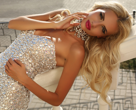 moda: all'aperto foto di moda di elegante bella donna con i capelli biondi in lussuoso abito paillettes e accessori in argento, in posa in estate parco