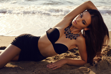 fashion outdoor photo of beautiful sexy girl with dark hair and tanned skin wears black bikini with luxurious necklace relaxing on summer beach