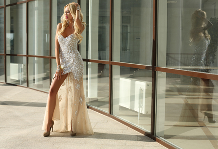 sensual girl: fashion outdoor photo of elegant beautiful woman with blond hair in luxurious sequins dress and silver accessories,posing in summer park