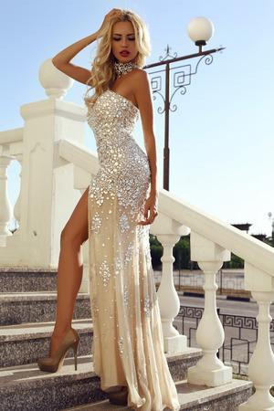 Mode im Freien Foto von eleganten schönen Frau mit blonden Haaren in luxuriösen Pailletten-Kleid und Silber Zubehör, posiert im Sommer Park