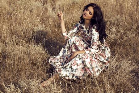 fashion outdoor foto van mooie sensuele vrouw met donker haar draagt luxe kleurrijke jurk met bloemen print, poseren in de zomer veld Stockfoto