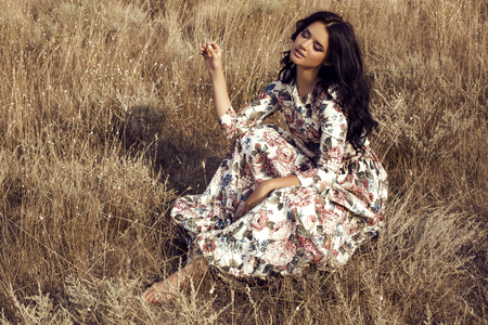 fashion outdoor photo of beautiful sensual woman with dark hair wears luxurious colorful dress with flowers print,posing in summer field