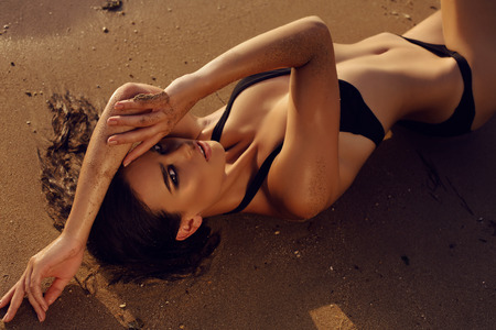 tan woman: fashion outdoor photo of beautiful sexy girl with dark hair and tanned skin wears black bikini relaxing on summer beach Stock Photo