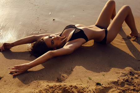 brunette girl: fashion outdoor photo of beautiful sexy girl with dark hair and tanned skin wears black bikini relaxing on summer beach Stock Photo