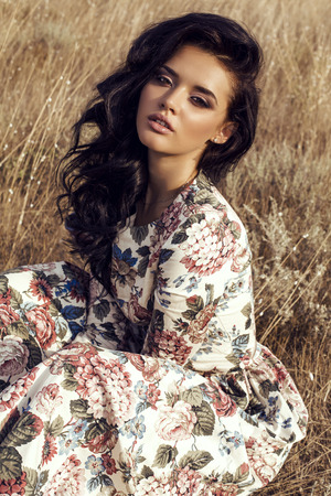 sensual: fashion outdoor photo of beautiful sensual woman with dark hair wears luxurious colorful dress with flowers print,posing in summer field