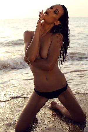 cabello negro: moda foto al aire libre de la hermosa chica sexy con el pelo oscuro y piel bronceada lleva bikini negro y los accesorios, relajarse en la playa de verano