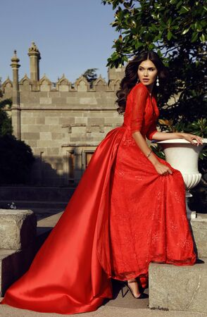 summer dress: fashion outdoor photo of beautiful woman with dark hair wears luxurious red dress,posing in summer park