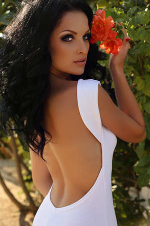 sexy fashion: fashion outdoor photo of beautiful sensual woman with dark hair in elegant white dress with open back posing in summer garden Stock Photo