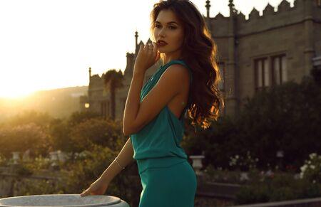 la foto all'aperto di modo di bella donna con capelli scuri porta il vestito elegante, posante nel parco dell'estate