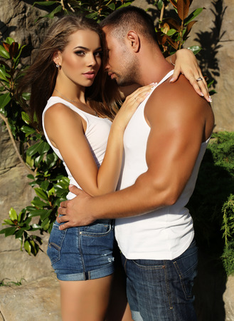 impassioned: fashion outdoor photo of sensual impassioned couple.beautiful gorgeous woman and tanned handsome man embracing in summer garden